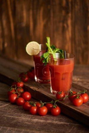 Photo pour Cocktail sanglant dans des verres avec de la chaux et du céleri sur fond de bois avec des tomates - image libre de droit