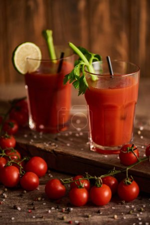Photo for Selective focus of bloody mary cocktail in glasses on wooden background with salt, pepper, tomatoes and celery - Royalty Free Image