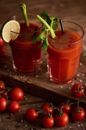 Photo pour Cocktail Mary sanglant dans des verres sur fond de bois avec sel, poivre, tomates et céleri - image libre de droit