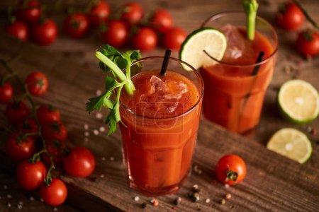 Photo pour Mise au point sélective de cocktails sanglants en verres sur fond de bois avec sel, poivre, tomates et céleri - image libre de droit