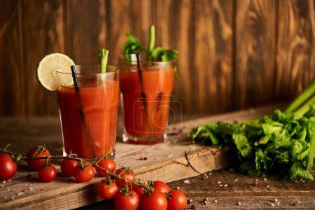 Photo pour Cocktail sanglant dans des verres sur fond de bois avec sel, poivre, tomates et céleri - image libre de droit