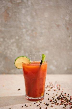 Photo pour Cocktail sanglant au sucre en verre avec chaux, céleri et paille sur fond gris avec poivre noir - image libre de droit