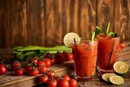 Photo pour Mise au point sélective de cocktails sanglants en verres sur fond de bois avec sel, poivre, chaux, tomates et céleri - image libre de droit