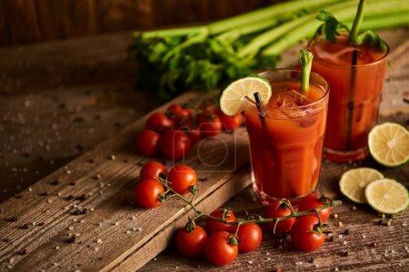 Photo pour Cocktail sanglant dans des verres sur fond de bois avec sel, poivre, chaux, tomates et céleri - image libre de droit