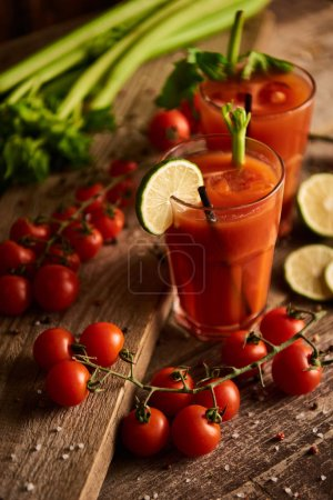 Photo for Selective focus of bloody mary cocktail in glasses on wooden background with salt, pepper, lime, tomatoes and celery - Royalty Free Image