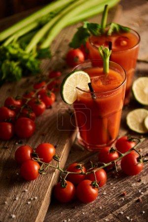 Photo pour Foyer sélectif de cocktail Mary sanglante dans des verres sur fond de bois avec sel, poivre, citron vert, tomates et céleri - image libre de droit