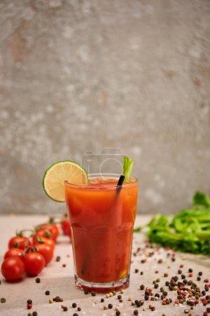 Photo pour Mise au point sélective d'un cocktail sanglant en verre avec de la paille et de la chaux près du sel, du poivre, des tomates et du céleri sur fond gris - image libre de droit