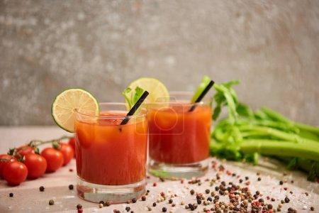 Photo pour Cocktail Mary sanglant dans des verres avec des pailles et du citron vert près de sel, poivre, tomates et céleri sur fond gris - image libre de droit