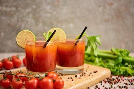 Photo pour Cocktail de Mary ensanglanté dans des verres avec pailles et citron vert sur une planche de bois près de sel, poivre, tomates et céleri - image libre de droit
