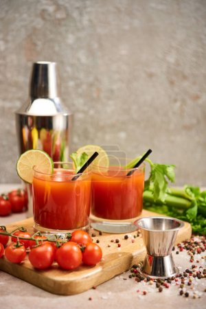 Photo for Bloody mary cocktail in glasses with straws and lime on wooden board near salt, pepper, tomatoes and celery - Royalty Free Image