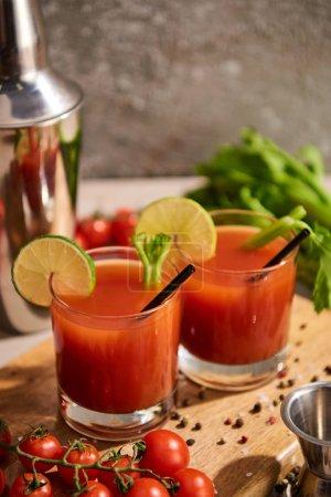 Photo pour Mise au point sélective de cocktails sanglants dans des verres sur des panneaux de bois près du sel, du poivre, des tranches de chaux, des tomates et du céleri - image libre de droit