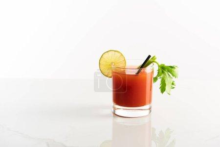 Photo pour Cocktail Mary sanglant en verre garni de citron vert et céleri isolé sur blanc - image libre de droit
