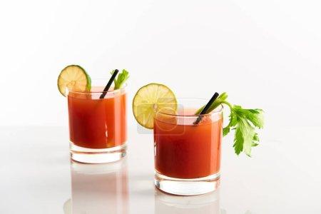 Photo pour Cocktail Mary sanglant dans des verres garnis de citron vert et céleri isolé sur blanc - image libre de droit