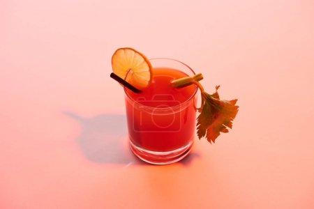 Photo pour Cocktail Mary sanglant dans un verre garni de citron vert et de céleri sur fond rouge illuminé - image libre de droit