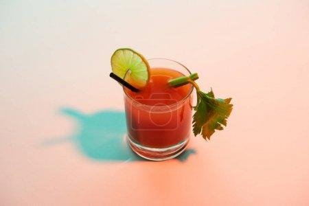 Photo pour Cocktail sanglant dans un verre garni de chaux et de céleri sur fond rouge et bleu illuminé - image libre de droit