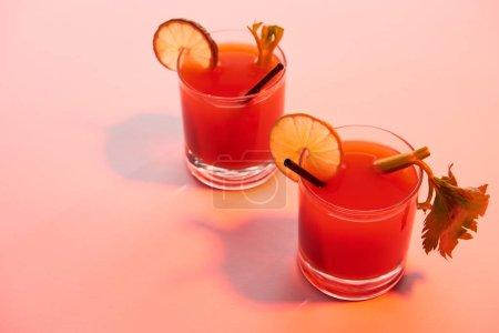 Photo pour Cocktail Mary ensanglanté dans des verres garnis de citron vert et de céleri sur fond lumineux rouge - image libre de droit