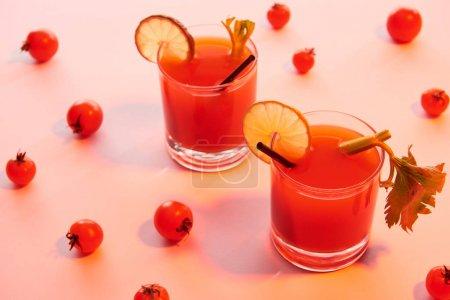 Photo pour Cocktail Mary sanglant dans des verres garnis de citron vert et de céleri sur fond rouge illuminé de tomates - image libre de droit