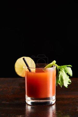 Photo pour Cocktail Mary sanglant en verre garni de citron vert et céleri isolé sur noir - image libre de droit