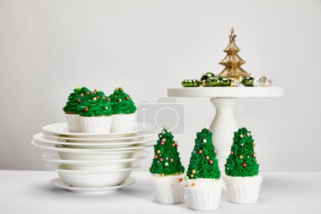 Photo for Delicious Christmas tree cupcakes with plates and shiny baubles on white surface isolated on grey - Royalty Free Image