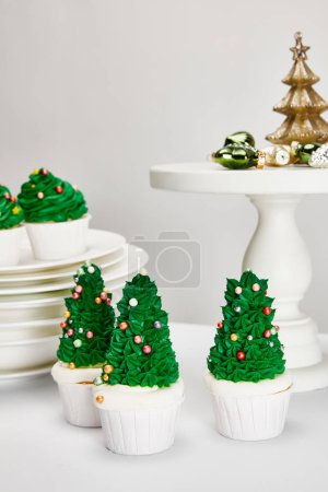 Foto de Delicious Christmas tree cupcakes with plates and shiny baubles on white surface isolated on grey - Imagen libre de derechos