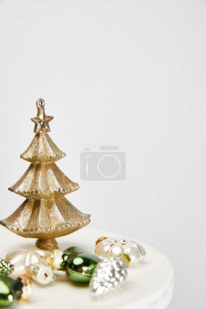 Photo for Shiny Christmas tree and baubles on white surface isolated on grey - Royalty Free Image