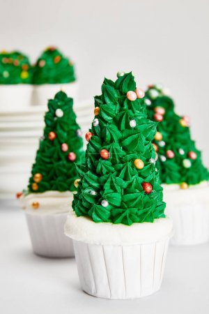 Photo for Delicious Christmas tree cupcakes on white surface isolated on grey - Royalty Free Image
