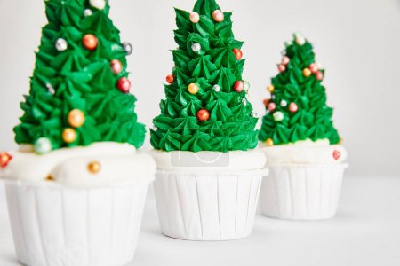 Foto de Selective focus of delicious Christmas tree cupcakes in row on white surface isolated on grey - Imagen libre de derechos