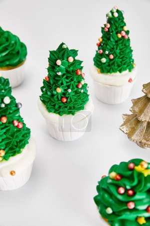 Foto de Delicious cupcakes and decorative golden Christmas tree on white surface - Imagen libre de derechos