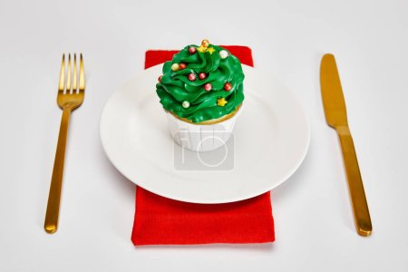 Photo for Delicious cupcake on white plate with golden cutlery and red napkin on white surface - Royalty Free Image