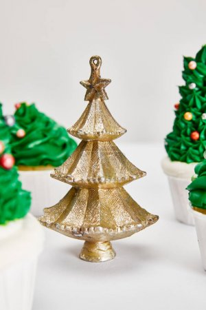 Photo for Selective focus of delicious cupcakes and decorative golden Christmas tree on white surface isolated on grey - Royalty Free Image