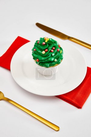 Foto de Delicious cupcake on white plate with golden cutlery and red napkin on white surface - Imagen libre de derechos