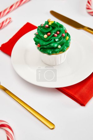 Photo for Delicious cupcake on white plate with golden cutlery, candies and red napkin on white surface - Royalty Free Image