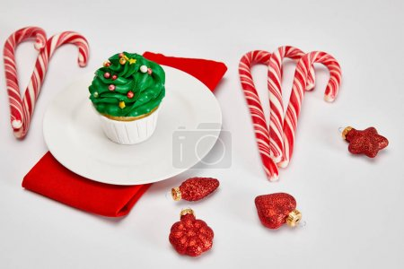 Photo for Delicious cupcake on white plate with candies, baubles and red napkin on white surface - Royalty Free Image