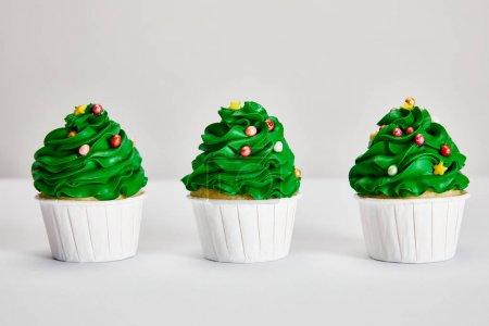 Foto de Tasty Christmas tree cupcakes in row on white surface isolated on grey - Imagen libre de derechos