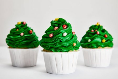 Photo for Selective focus of tasty Christmas tree cupcakes in row on white surface isolated on grey - Royalty Free Image