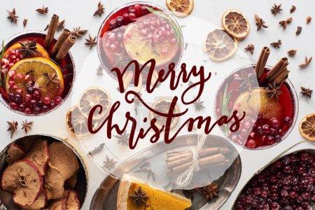 Foto de Vistas superiores de cócteles de christmas con naranja, granada, canela, pastel en la bandeja, manzanas secas y fresa congelada con ilustración de madroños de mermelada. - Imagen libre de derechos