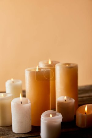 Photo for Close up of burning candles on wooden table on beige - Royalty Free Image
