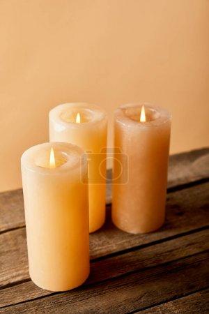 Foto de Three burning candles on wooden table on beige - Imagen libre de derechos