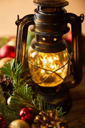 Photo for Close up of decorative vintage oil lamp with blurred lights, spruce branches and christmas balls - Royalty Free Image