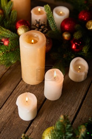 burning candles with spruce branches and christmas balls on wooden table