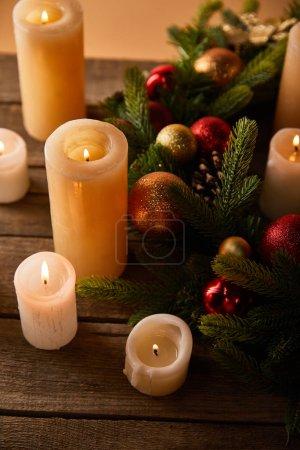 Photo pour Brûler des bougies avec des branches d'épinette et des boules de Noël sur une table en bois - image libre de droit