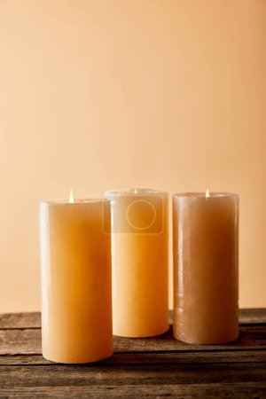 Photo pour Three festive burning candles on wooden table on beige - image libre de droit