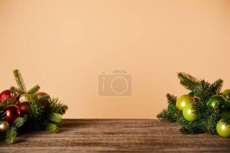 Photo pour Branches d'épinette avec boules de Noël sur table en bois beige - image libre de droit