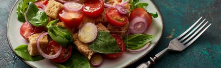 Photo for Fresh Italian vegetable salad panzanella served on plate on textured table with fork, panoramic shot - Royalty Free Image