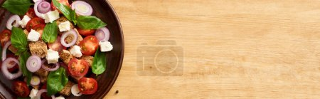 Photo for Top view of fresh Italian vegetable salad panzanella served on plate on wooden table, panoramic shot - Royalty Free Image