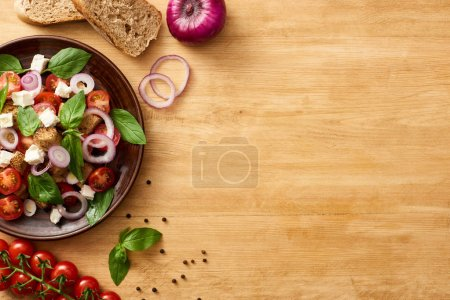 Photo for Top view of delicious Italian vegetable salad panzanella served on plate on wooden table near fresh ingredients - Royalty Free Image