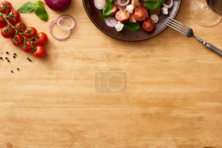 Photo for Top view of delicious Italian vegetable salad panzanella served on plate on wooden table near fresh ingredients and red wine - Royalty Free Image
