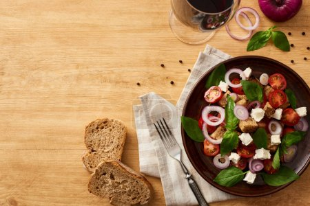 Photo for Top view of delicious Italian vegetable salad panzanella served on plate on wooden table near fresh ingredients, fork, bread and red wine - Royalty Free Image