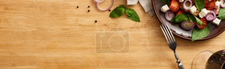 Photo for Top view of delicious Italian vegetable salad panzanella served on plate on wooden table near fresh ingredients, fork and red wine, panoramic shot - Royalty Free Image