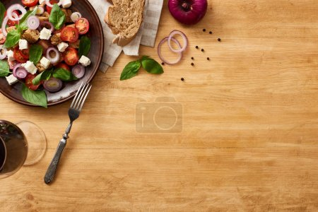 Photo for Top view of delicious Italian vegetable salad panzanella served on plate with fork on wooden table near fresh ingredients on napkin and red wine - Royalty Free Image